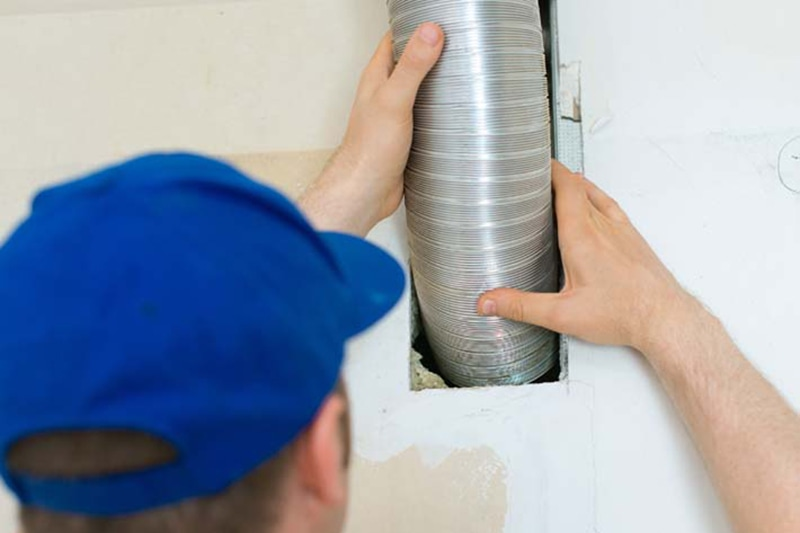 Man setting up ventilation system indoors for a customers split-system AC unit