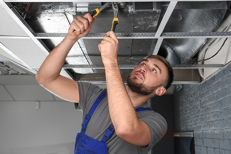 Male technician repairing air conditioner indoors, Does SEER Save Money? | HVAC Energy Efficiency | Sutton Brothers