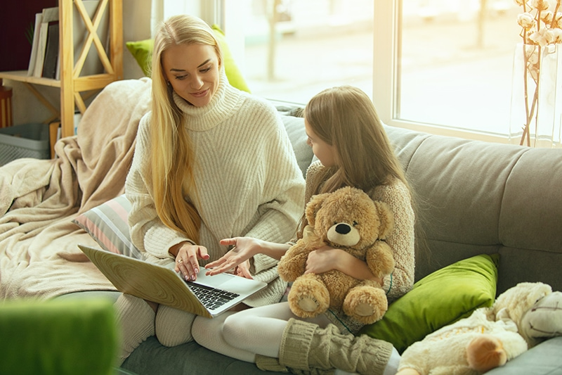 Mother and daughter sitting on a coach watching a movie on a laptop, The Basics of Winter Indoor Air Quality | Winston-Salem | Sutton Brothers