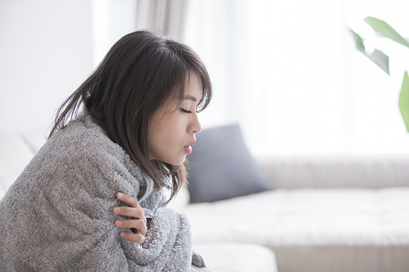 Woman cold indoors wrapped in blanket, Why Is My Furnace Blowing Out Cold Air?   HVAC   Winston-Salem