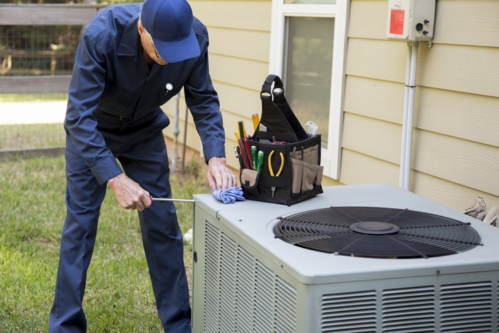 Senior Adult air conditioner Technician/Electrician performs HVAC maintenance on an outdoor unit.