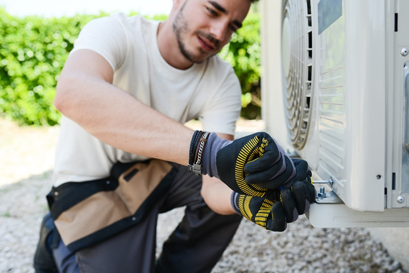 Young man electrician repairing air conditioning in client house, Repair or Replace Your AC? 5 Factors to Help | HVAC Service