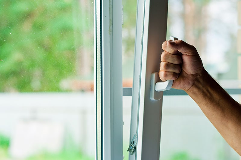 Man opens the plastic window to let in fresh spring air, Indoor Air Quality