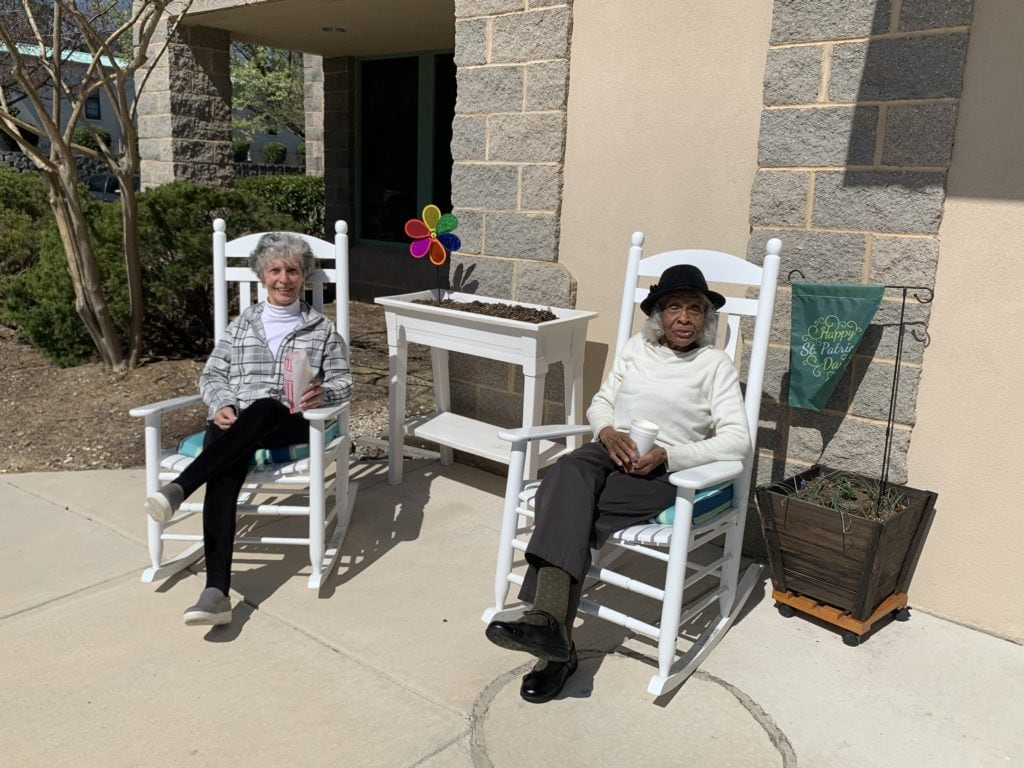 Two senior citizens outside sitting on white rocking chairs