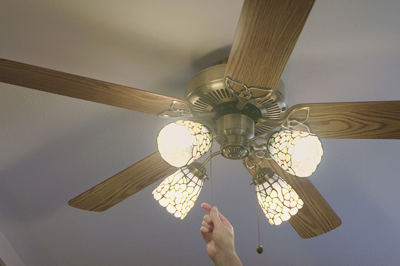 a person turning on their ceiling fan in order to save energy and keep their Kernersville home cool