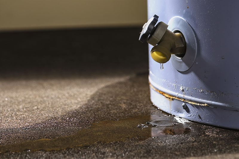 Water leaking from the plastic faucet on a residential electric water heater sitting on a concrete floor. Water Heater Problems