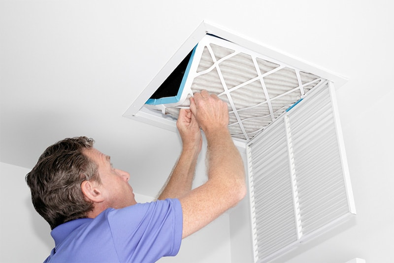 Middle aged man replacing fillter, Do Air Filters Work?   Indoor Air Quality, HVAC Service   Kernersville, NC