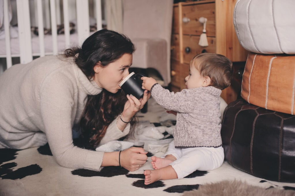 how to save money on your heating bill this winter, happy mother and baby playing together at home