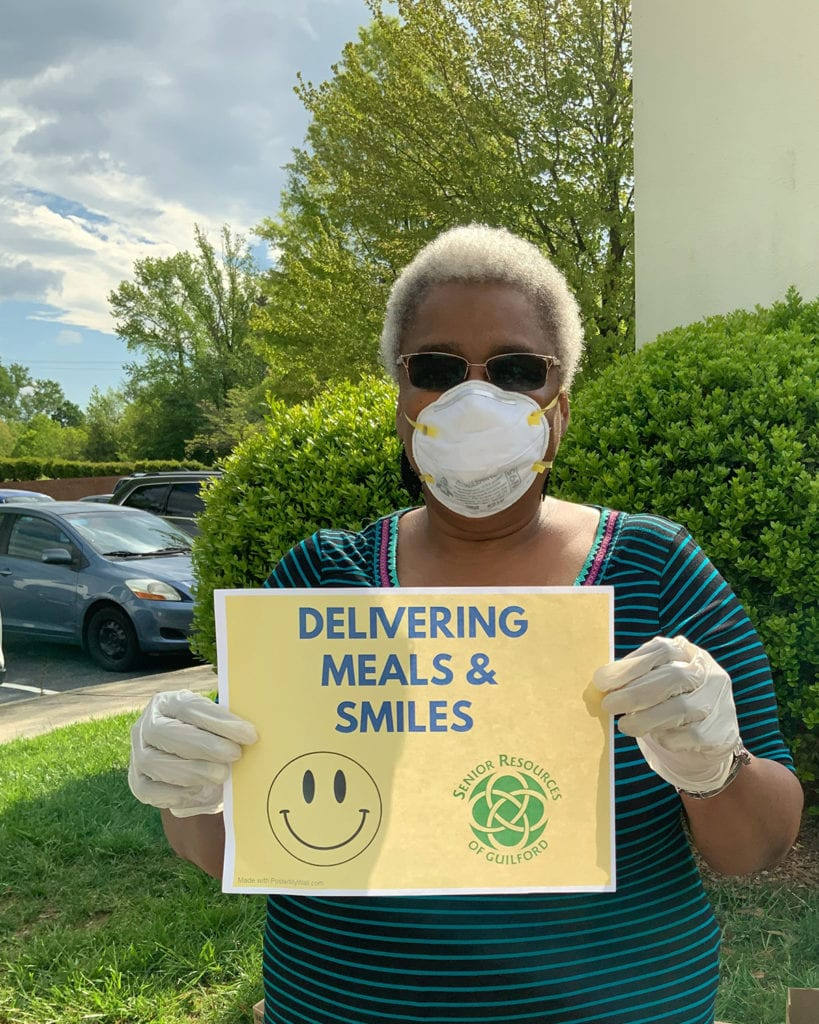 Woman outside wearing a mask & holding a sign that reads delivering meals & smiles