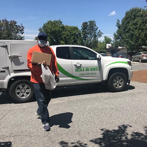 Man outside wearing a mask & delivering meals